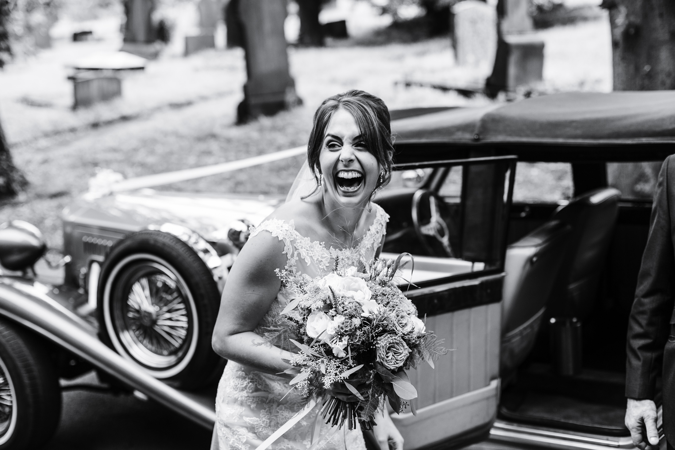 smiling bride in front of wedding car